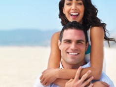 Portrait of a happy young couple enjoying on beach